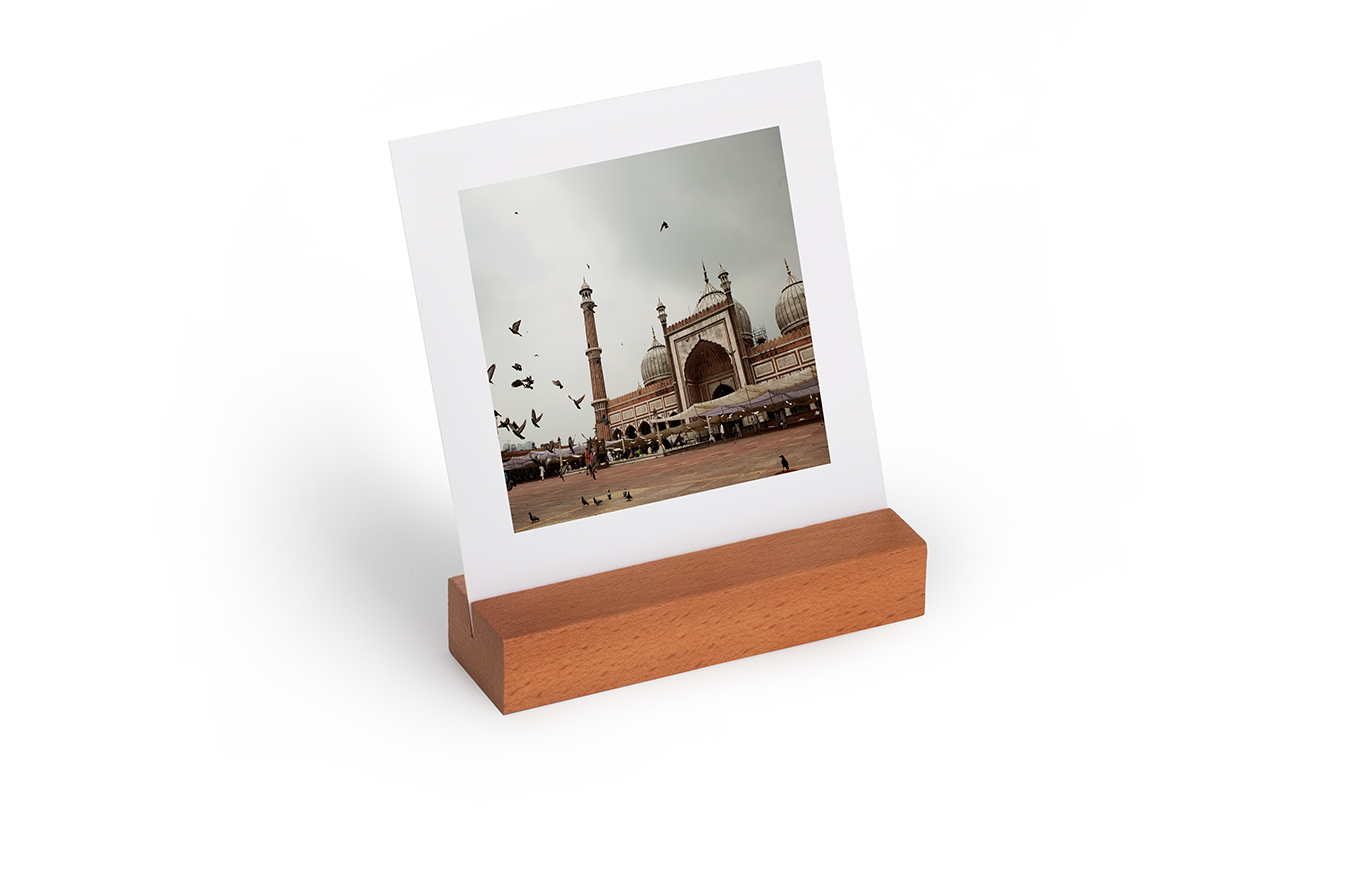 A mini travel art print sitting in its wooden display block.
