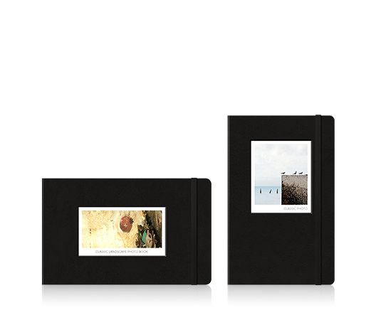 Two Moleskine photo books. One landscape photo book with an artwork on the cover and one portrait photo book with birds at the beach on the cover