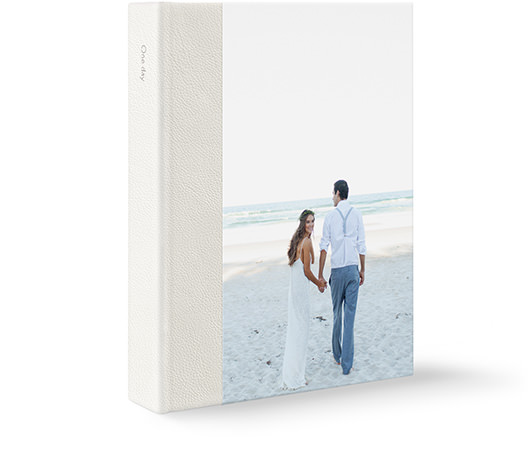 Large leather portrait wedding photo album with a newlywed couple at the beach on the cover.