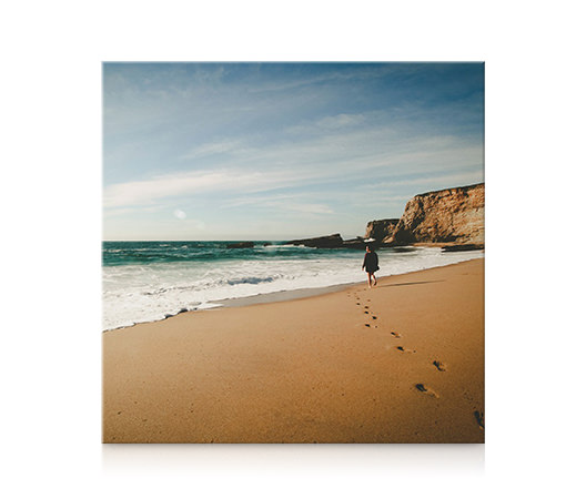A square canvas print of a woman walking along the beach hanging on a wall.