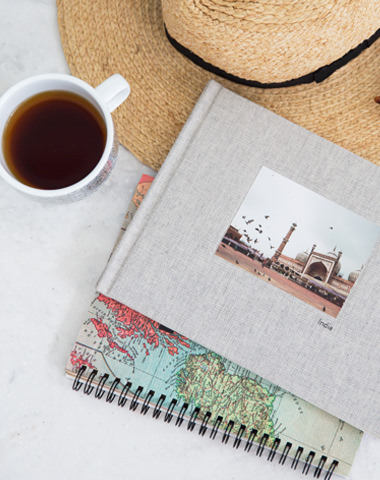 A notebook with a travel photo book laying on top laying on a table next to a tea and sun hat.