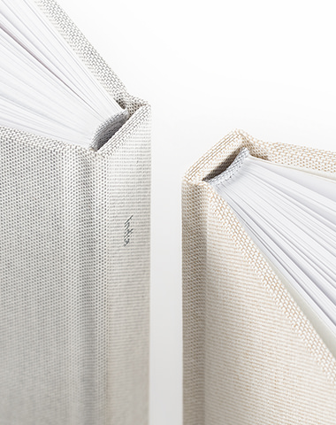 Two linen photo books back to back showing the spine and page detail.