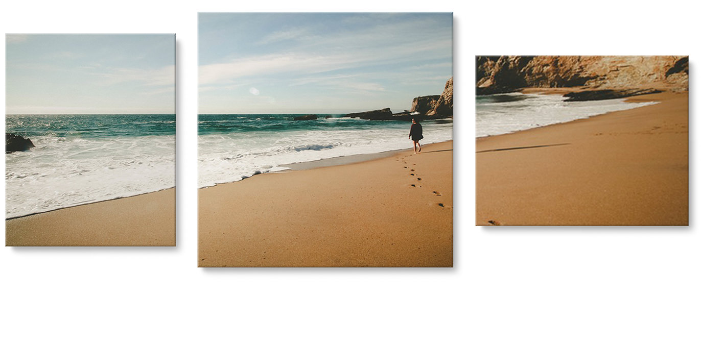 Three canvas prints of a beach hanging on a wall. One portrait canvas, one square canvas and one landscape canvas.