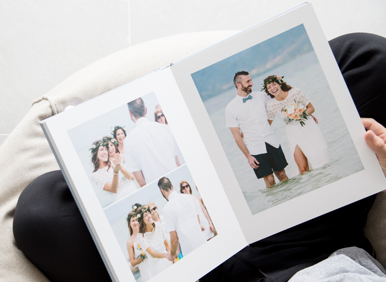 Open page of wedding photo album showing three photos of couple on their wedding day
