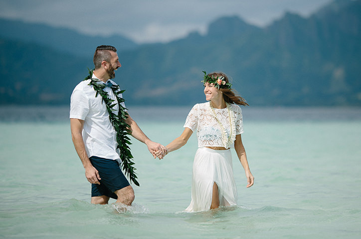 Couple standing in water on their wedding day.
