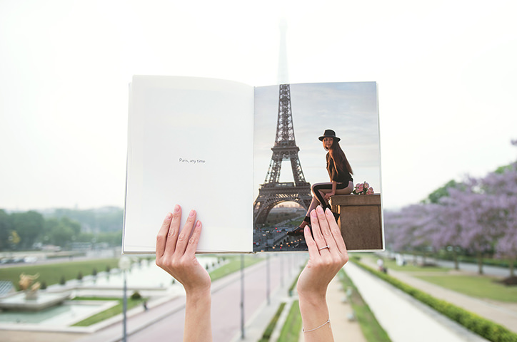 Hands holding portrait photo book with image of Eiffel tower in front of the Eiffel tower.