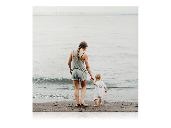Square canvas print of mother and her child holding hands and dipping their feet in the water at the beach.