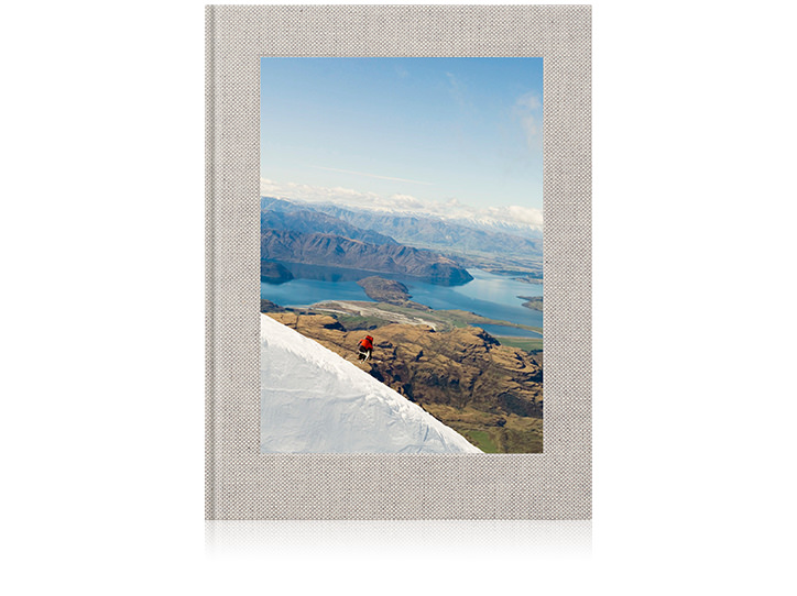 Premium linen travel portrait photo book with mountains and lake scenery on the cover.