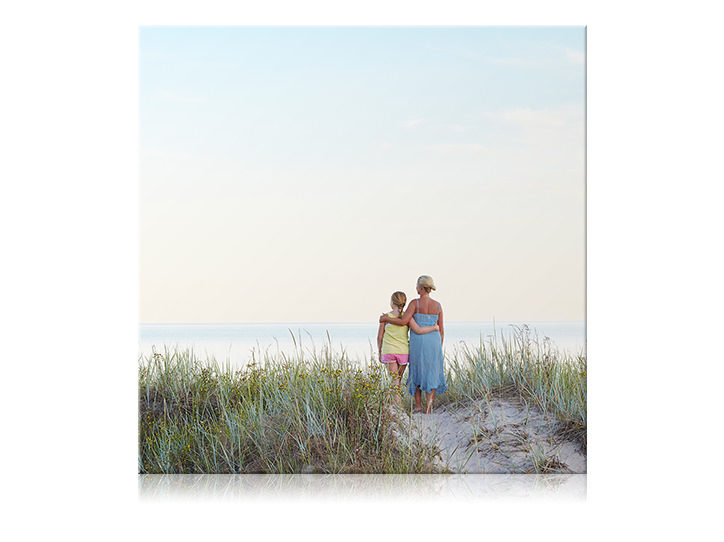 Square canvas print of mother and daughter with arms around each other at the beach.