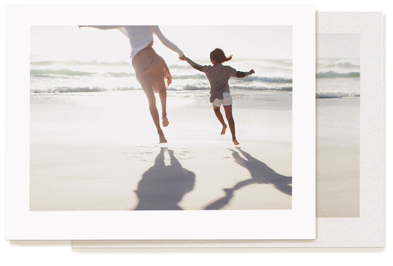 Image of printed photo on MILK Photo Lustre paper. Photo is of woman and girl running on beach hand in hand