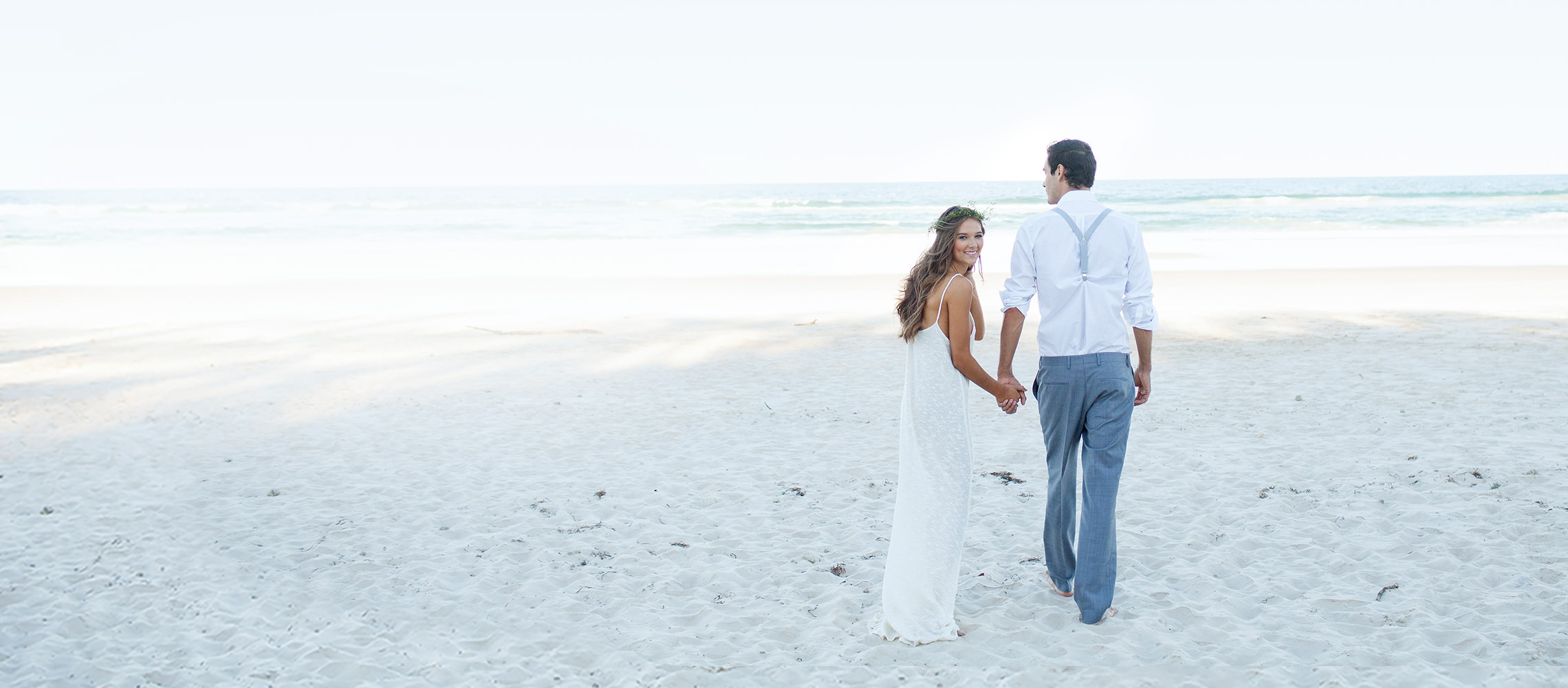 Couple holding hands at the beach on their wedding day.