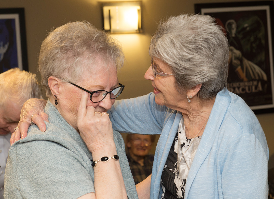 Two older women embracing.
