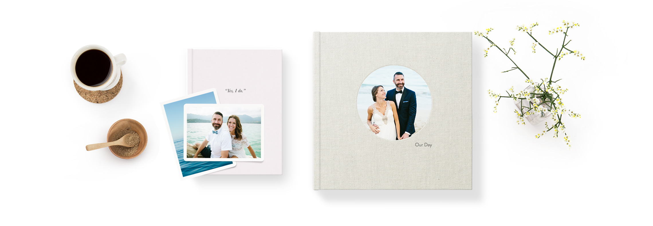 Photo book, photo album and art prints set on a white table with coffee cup and vase of flowers.