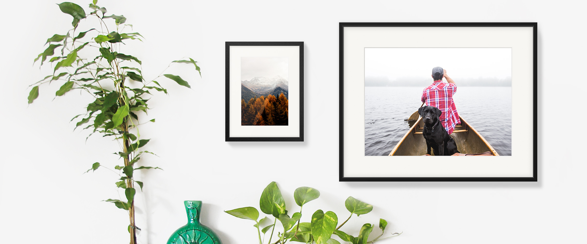 Two hanging gallery frames side by side on a white wall; one is an image of autumnal trees, the other is a man and his dog on a canoe.