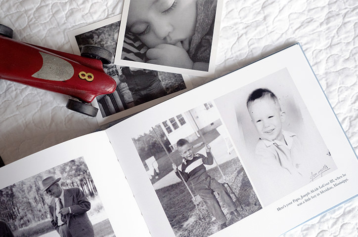 Open photo book alongside printed black and white photos