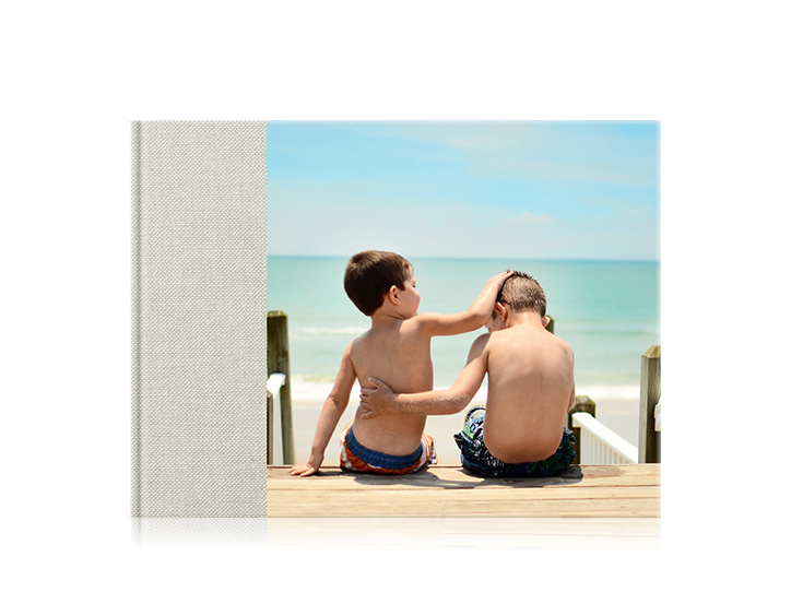 Landscape premium family photo book with a 3/4 cover of two brothers at the beach with arms around each other.