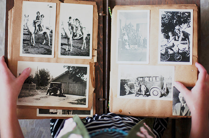 Hands holding traditional scrapbook filled with vintage photographs.