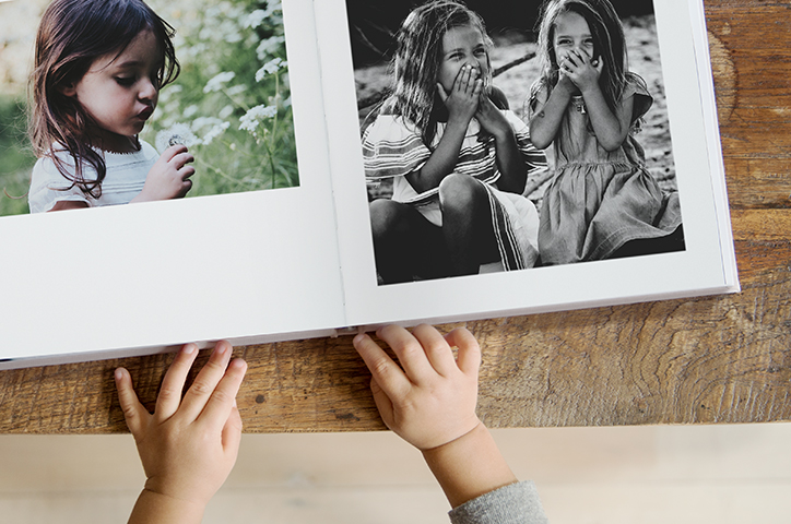 Open photo book with images of young girls smiling, set on a wooden table.