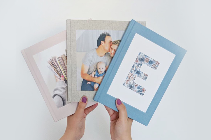 Hands holding three photo books in a fan shape.