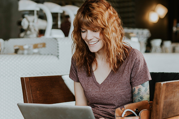 Red-headed woman in cafe setting on a wooden chair smiling and looking at her laptop screen.
