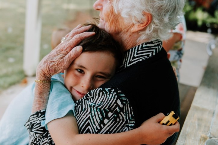 A young child smiling at the camera being embraced in a hug by an older woman.