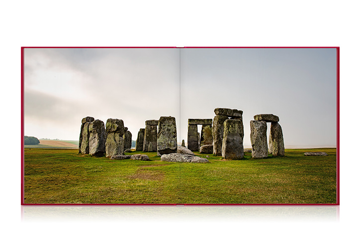 Square travel photo book laying open with a photo of the Stonehenge.