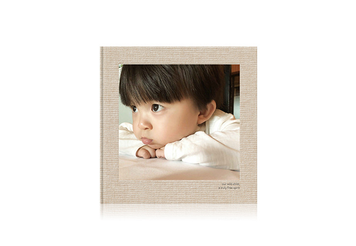 Square linen baby photo book with a toddler on the front cover.