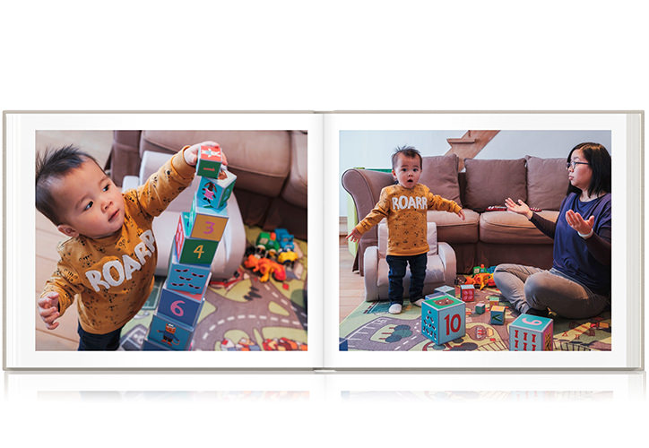 Landscape family photo book laying open with two photos of a mother and her son playing with toys in the living room