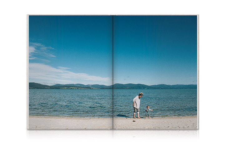 Portrait family photo book laying open with a photo of a mother and her son playing in the shallow water at the beach.