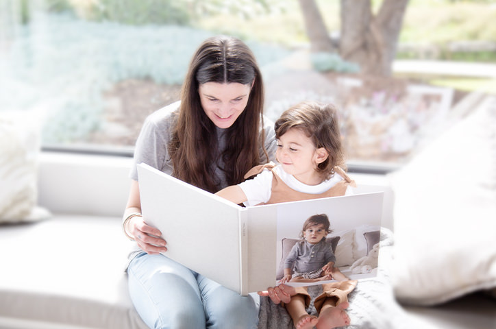 A mother and child sitting in front of a window smiling and flipping through the pages of a photo book together.