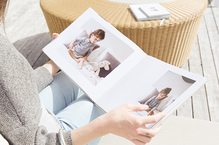 An over the shoulder shot of a woman sat outdoors in the sun flipping through the pages of a photo book featuring images of her young child.