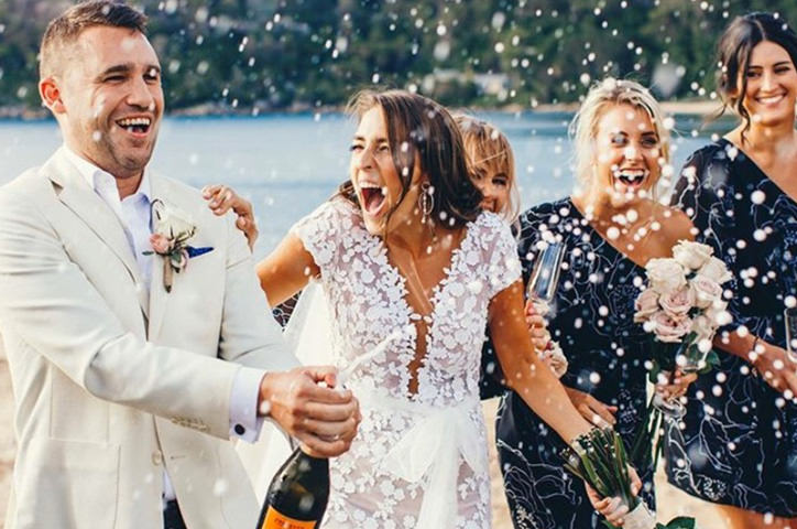 Couple popping champagne on their wedding day.