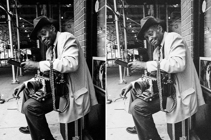 Black and white photo of man sat on the street with an old camera.