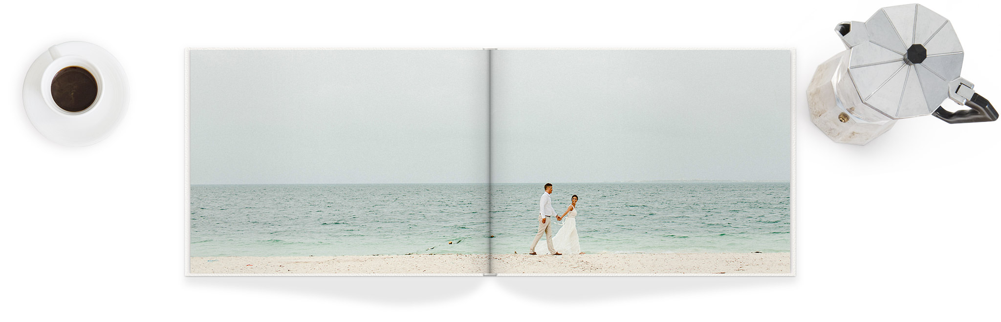 Photo Book open to a full page spread with an image of newlyweds walking hand in hand on a beach.